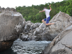 young man jumping off rocks into water - Missouri Vacations
