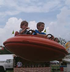 boys riding in carnival ride - Missouri Vacations