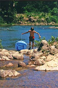 young man carrying raft over rocks - Missouri Vacations